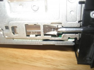 This shows how the tabs hold the radio in.  The nail presses the tab toward the center of the radio and it releases from the mount.